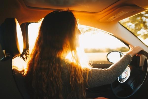 Mujer joven conduciendo coche.
