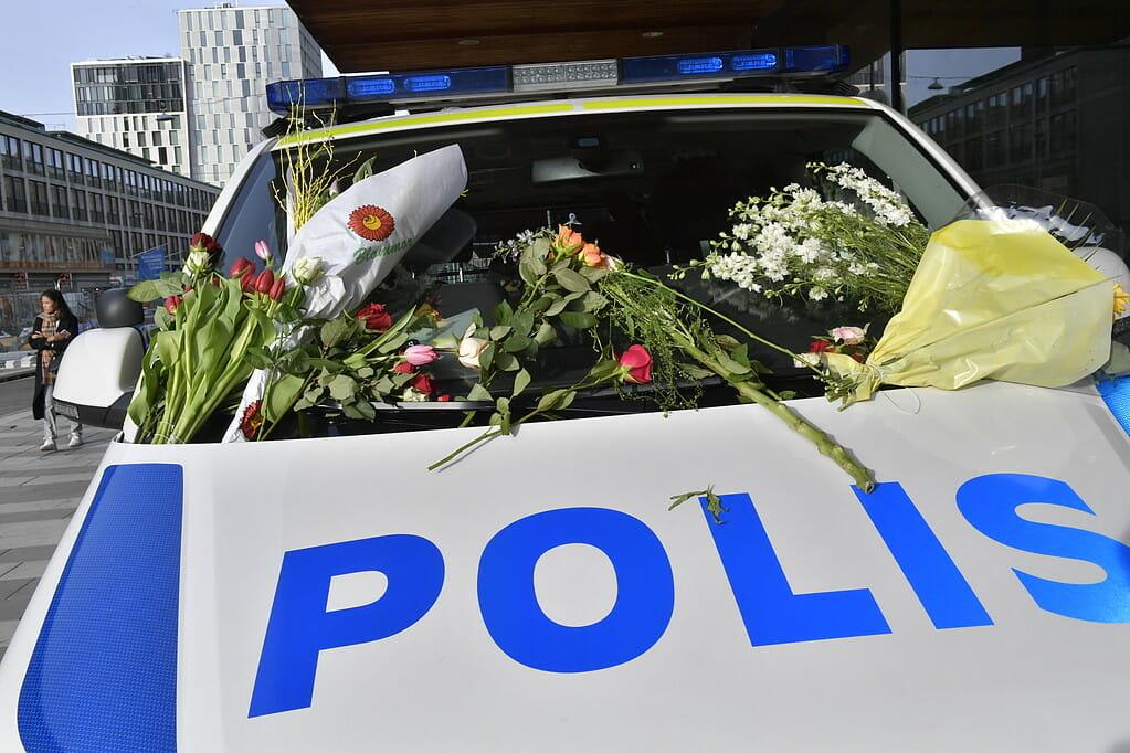 STOCKHOLM 2017-04-09 Blommor på en polisbil. Människor samlas och lämnar blommor utanför Åhléns City i centrala Stockholm för att hedra offren för fredagens terrorattack på Drottninggatan. Det var i fredags som en man i en kapad lastbil körde på ett stort antal personer på Drottninggatan. Fyra personer dödades och 15 skadades. Foto: Jonas Ekströmer / TT