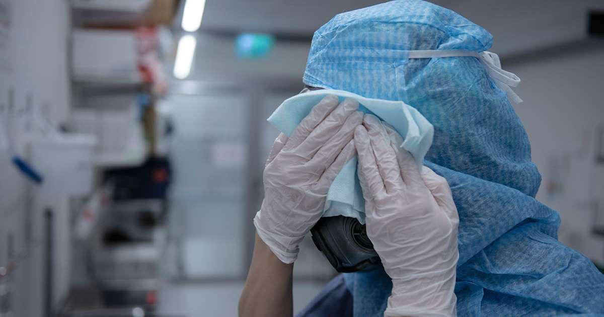 Sjuksköterska torkar svetten under pandemin.