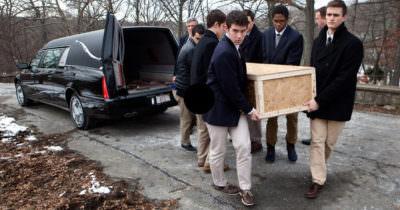 Chłopcy niosą trumnę na pogrzebie samotnego mężczyzny