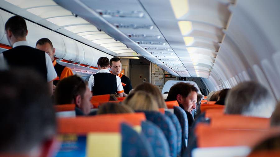Zdjęcie przedstawia pokład samolotu, na którym znajdują się pasażerowie oraz załoga