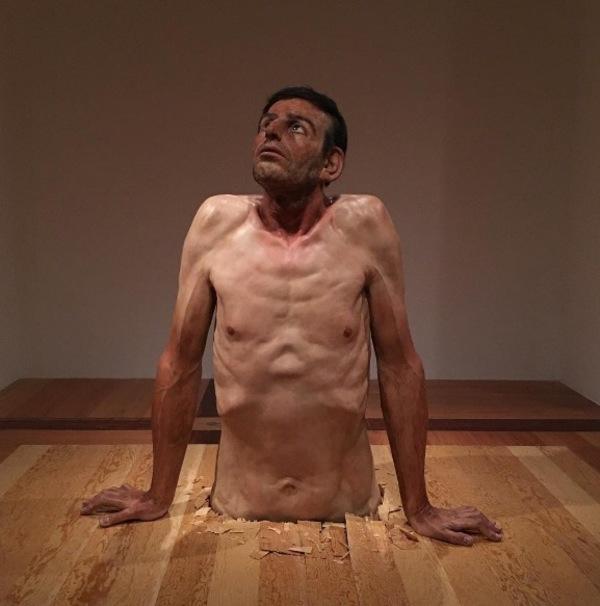Zdjęcie przedstawia hiperrealistyczną rzeźbę mężczyzny wyłaniającego się z podłogi, widzianego od pasa w górę