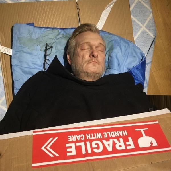 Zdjęcie przedstawia hiperrealistyczną rzeźbę bezdomnego mężczyzny