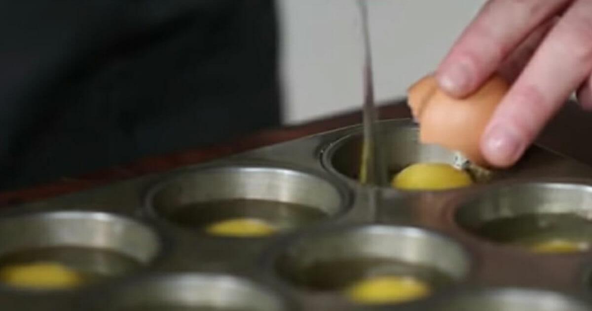 Na zdjęciu szef kuchni wbija po jednym jajku do każdego zagłębienia formy