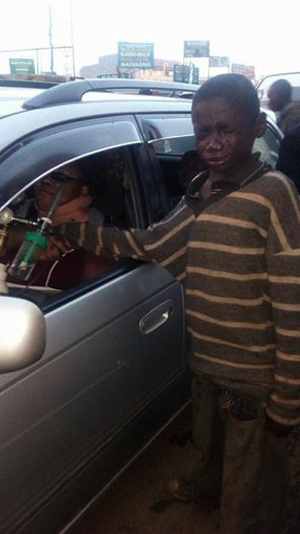 Zdjęcie przedstawia płaczącego Johna, który podaje rękę siedzącej w samochodzie Gladys