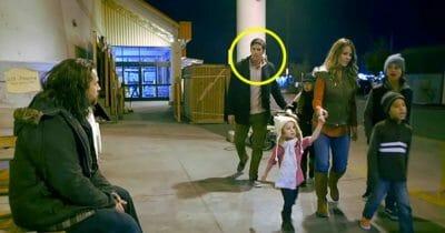Zdjęcie przedstawia rodzinę przechodzącą obok bezdomnego mężczyzny