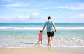 Na zdjęciu znajdują się ojciec z córką, którzy wspólnie spacerują po plaży
