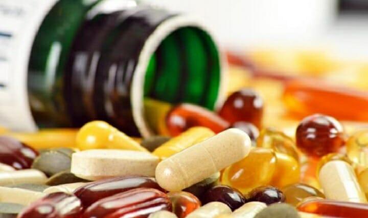 Na zdjęciu znajduje się flakonik, z którego wysypują się tabletki