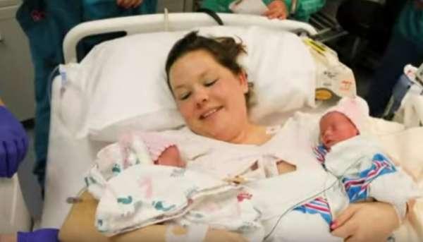Na zdjęciu znajduje się mama, która niedługo po porodzie trzyma w ramionach niemowlęta