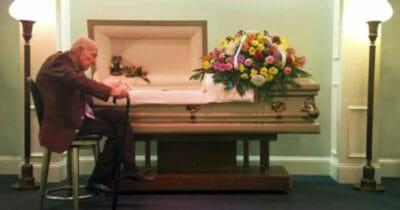 Na zdjęciu widać starszego mężczyznę, który siedzi przy trumnie zmarłej żony