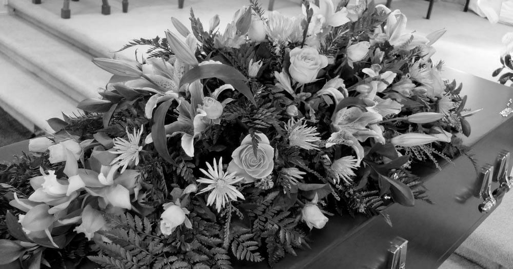 Na zdjęciu znajduje się położony na trumnie wieniec pogrzebowy