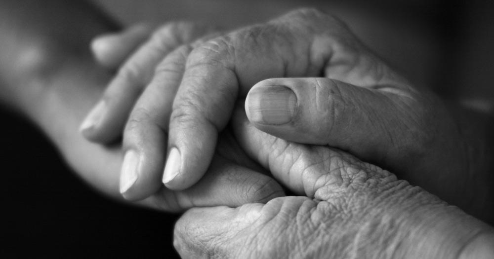 Na zdjęciu znajdują się splecione dłonie starszych osób