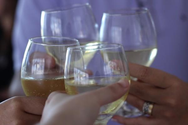 Na zdjęciu znajdują się trzymane w dłoniach kieliszki szampana