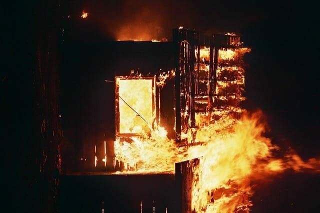 Na zdjęciu znajduje się płonący dom