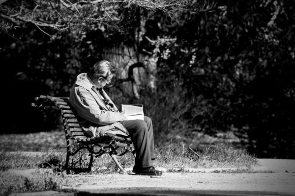 Na zdjęciu znajduje się starszy mężczyzna, który siedzi na ławce i czyta książkę