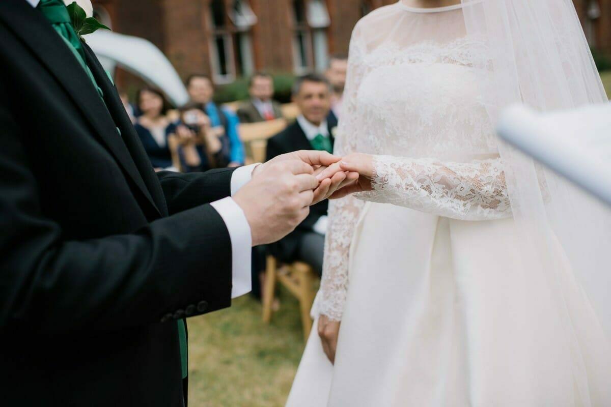 Na zdjęciu widać dłonie pary młodej podczas wymiany obrączek