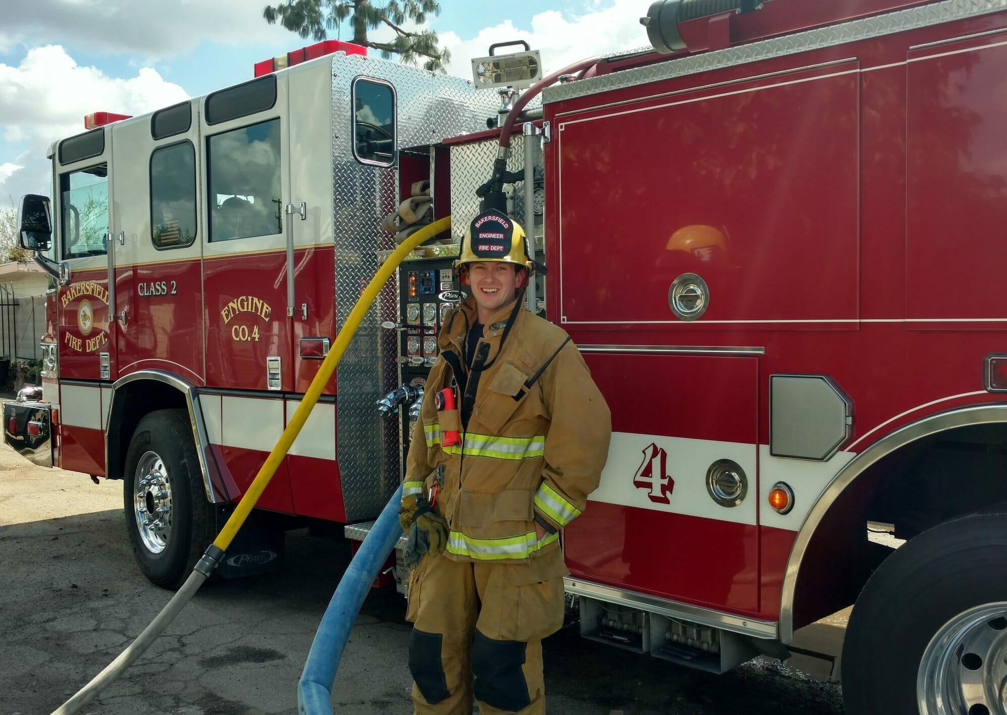 Na zdjęciu znajduje się strażak na tle wozu strażackiego