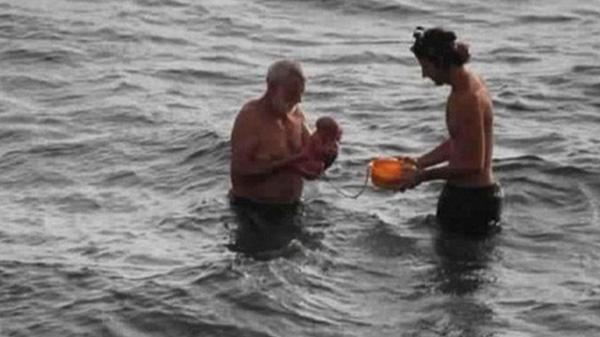 Na zdjęciu widać lekarza trzymającego na rękach dziecko i ojca dziecka z miską, w której znajduje się łożysko