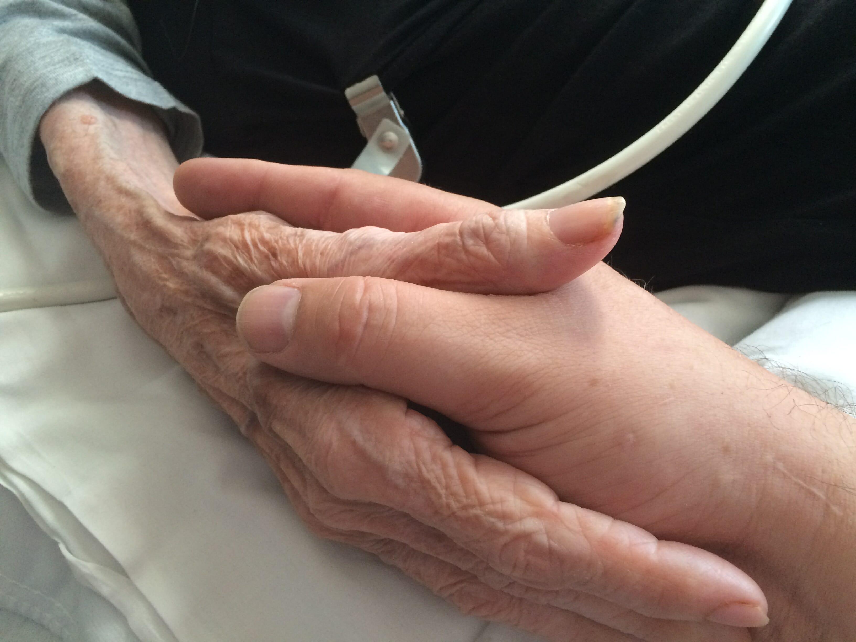 Na zdjęciu znajdują się splecione dłonie starszych ludzi
