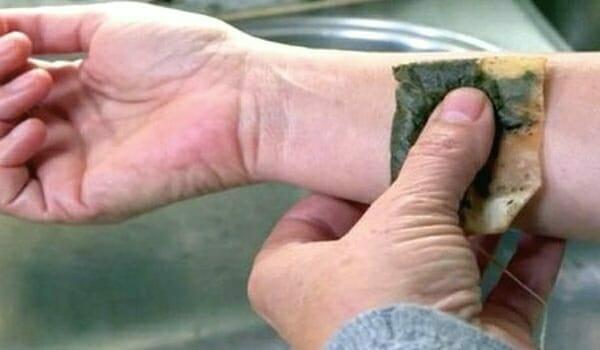 Osoba przykładająca mokrą torebkę z herbatą do swojego nadgarstka