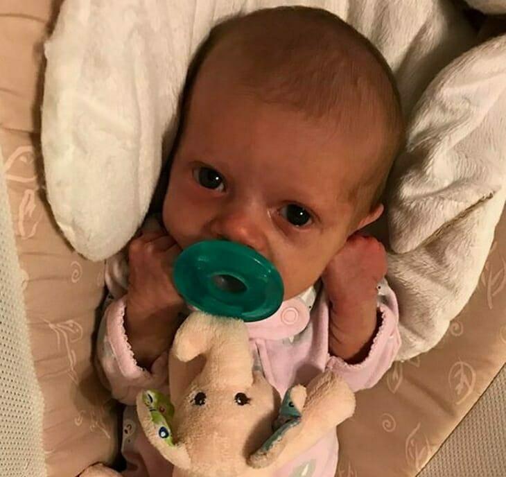 Mała Lucy ze smoczkiem i zaciśniętymi piąstkami