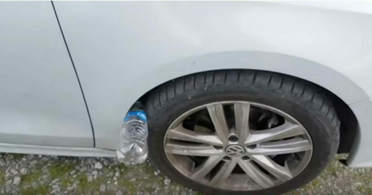 Plastikowa butelka wsadzona między koło a błotnik samochodu