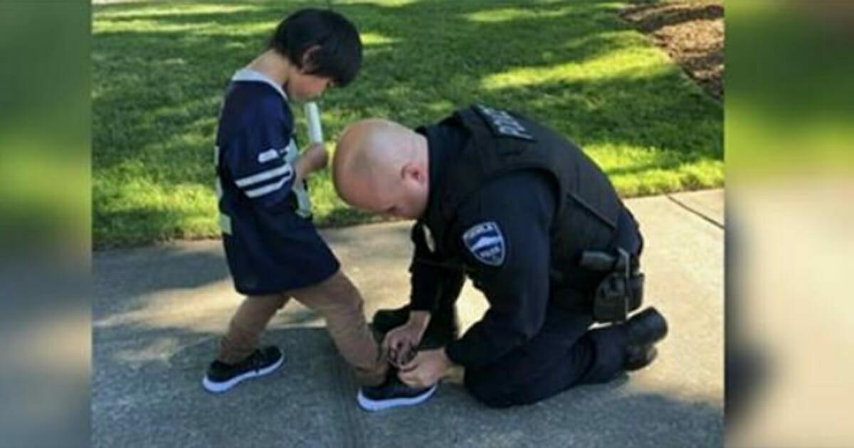 Policjant zakłada buty małemu chłopcu