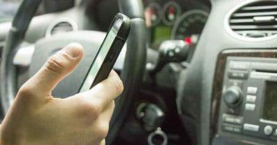 Dłoń osoby, która korzysta z telefonu komórkowego podczas prowadzenia samochodu