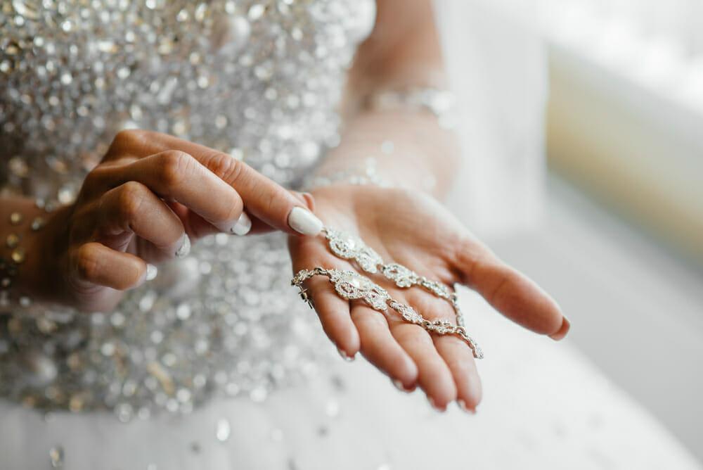 Dłonie panny młodej - kobieta trzyma w nich biżuterię