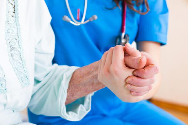 Lekarka trzyma za rękę starszą osobę