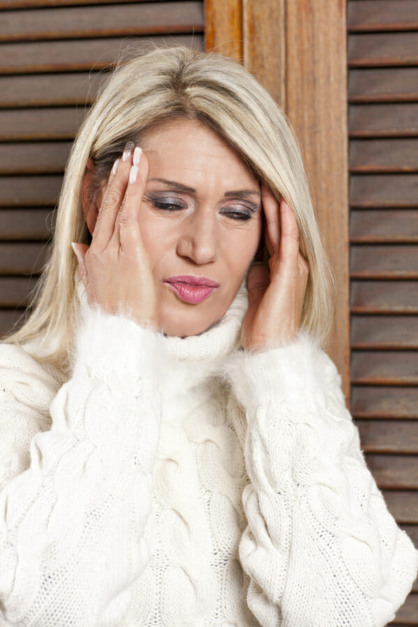Kobieta trzyma się za skronie - cierpi na ból głowy