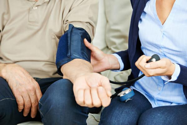 Kobieta mierzy mężczyźnie ciśnienie krwi
