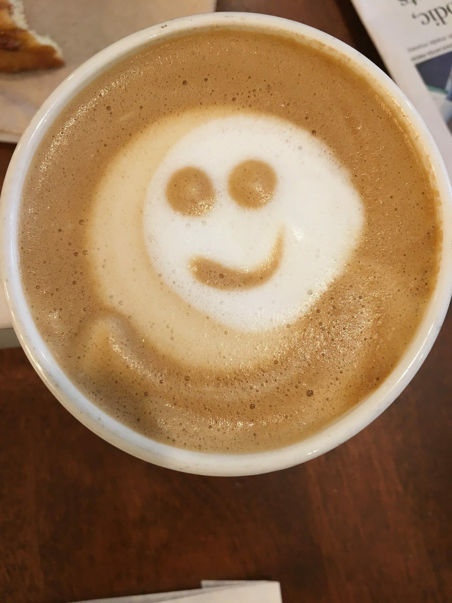 Rzut z góry na filiżankę kawy - pianka została ułożona w kształt uśmiechniętej buźki