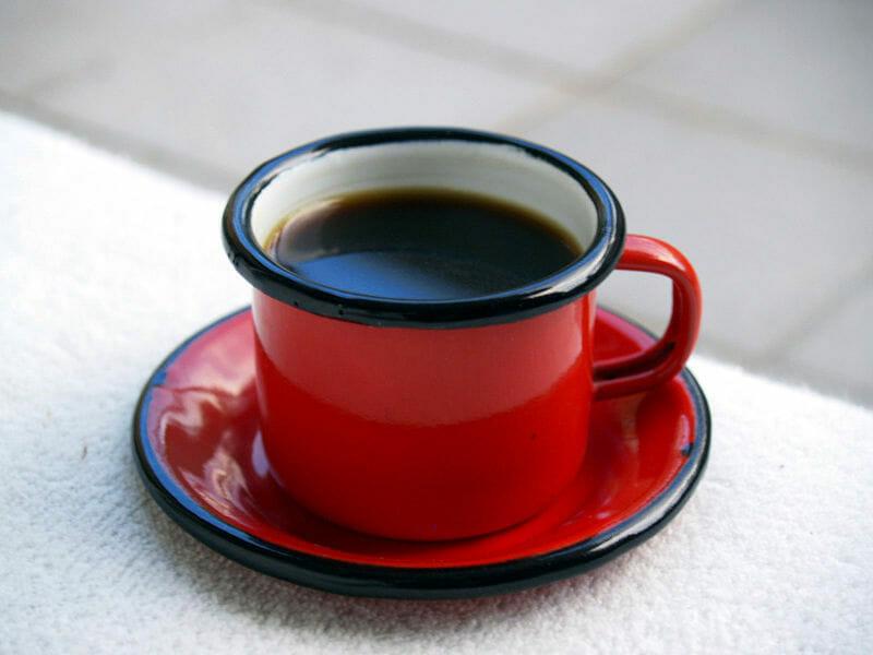Emaliowany garnczek na podstawce - w środku znajduje się czarna kawa