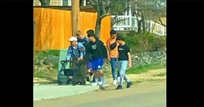 Grupa nastolatków asekuruje starszego mężczyznę podczas jego powrotu do domu