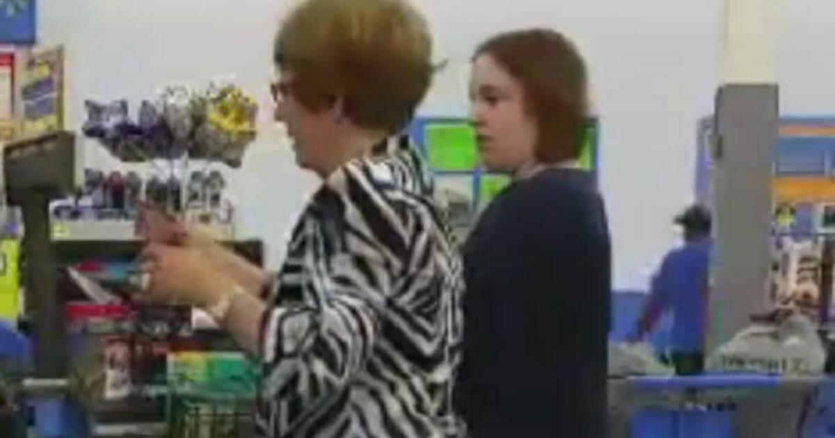dwie kobiety przy kasie - jedna płaci za pieluchy