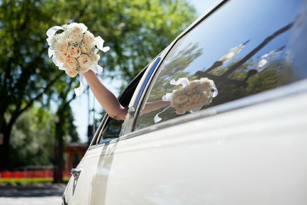 Panna młoda wystawia bukiet ślubny przez okno limuzyny, którą jedzie do ślubu