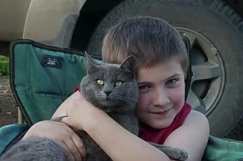 Uśmiechający się Liam przytula kota