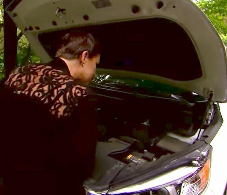 kobieta zagląda pod maskę samochodu