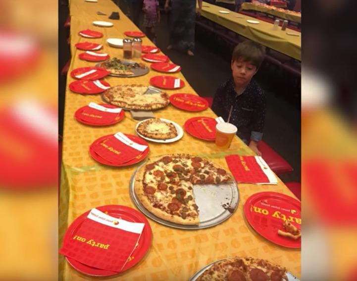 chłopiec siedzi przy stole z pizzą