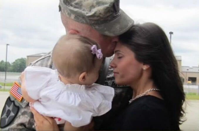 żołnierz trzyma na rękach dziecko i całuje kobietę
