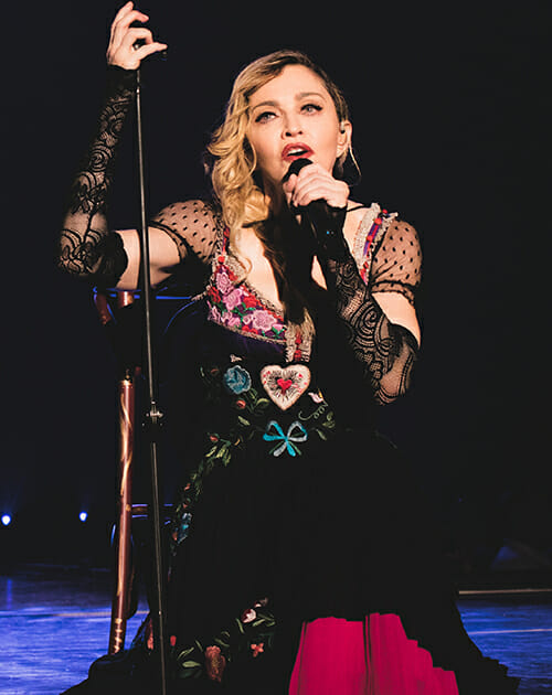 a woman is kneeling singing into a microphone