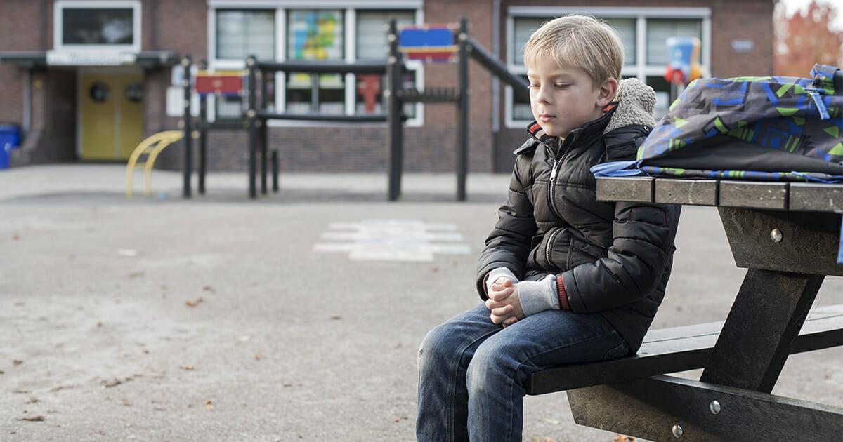 chłopiec siedzi sam na placu zabaw