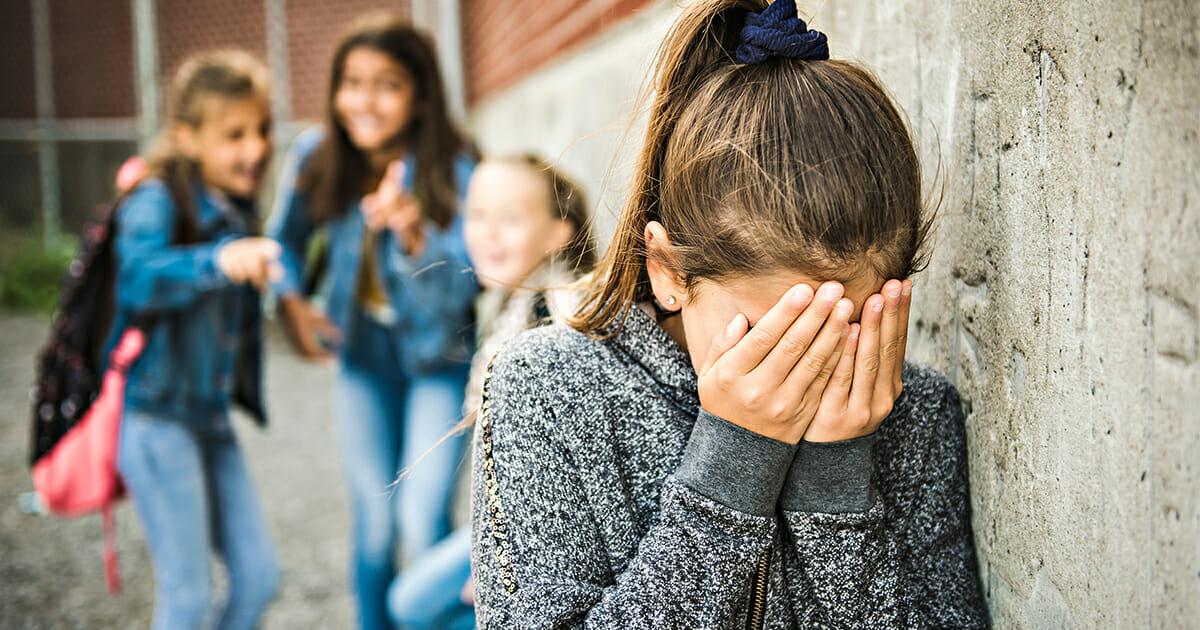 dziewczynka zakrywa twarz rekami, a inni się z niej śmieją