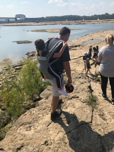 ludzie spacerują po skalnej plaży