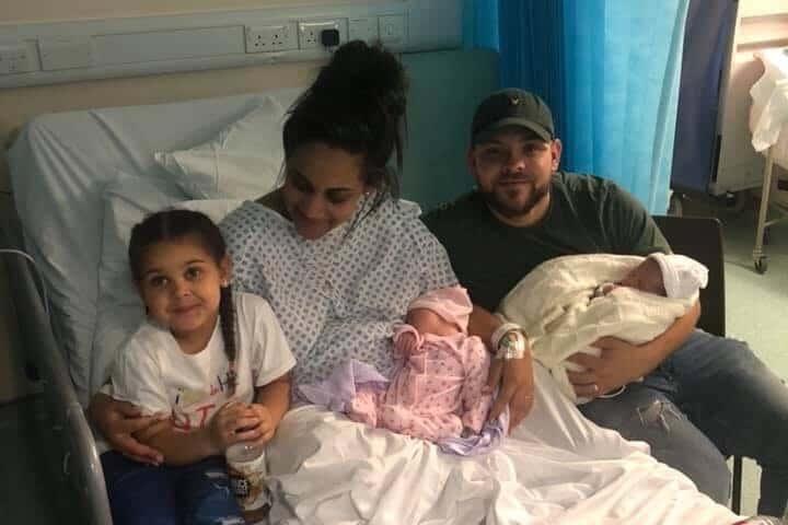 kobieta leży w łózki szpitalnym, są dzieci i mężczyzna