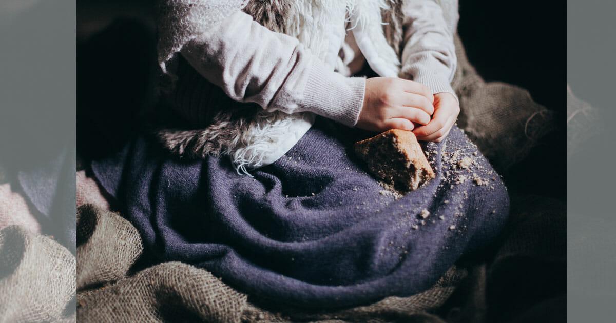 kobieta trzyma na kolanach kawałek chleba