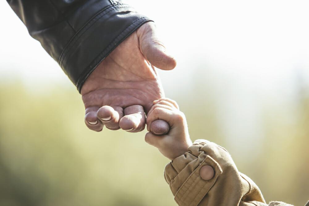 dorosły i dziecko trzymają się za rękę