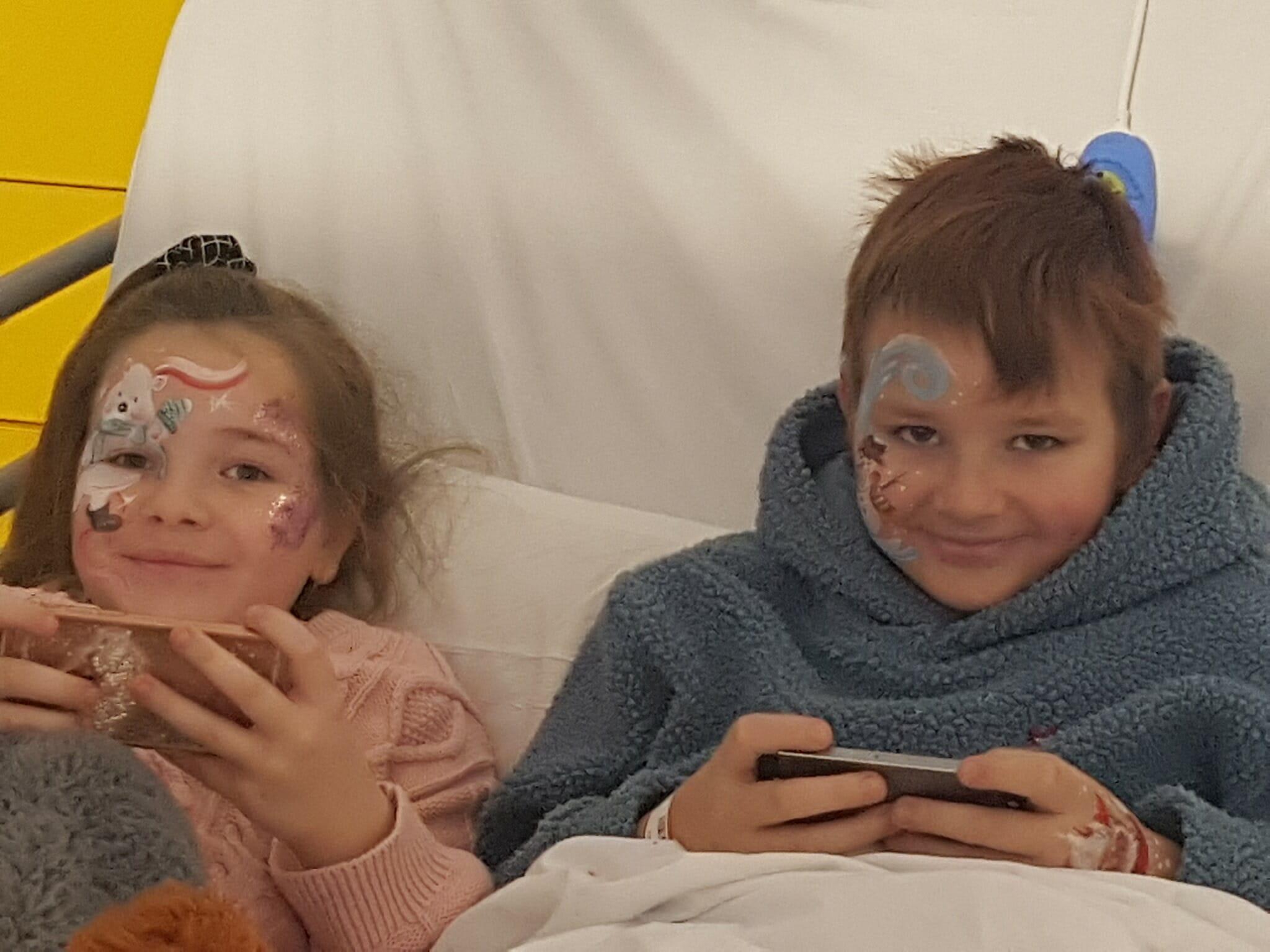 dzieci z pomalowanymi twarzami leżą w łóżku