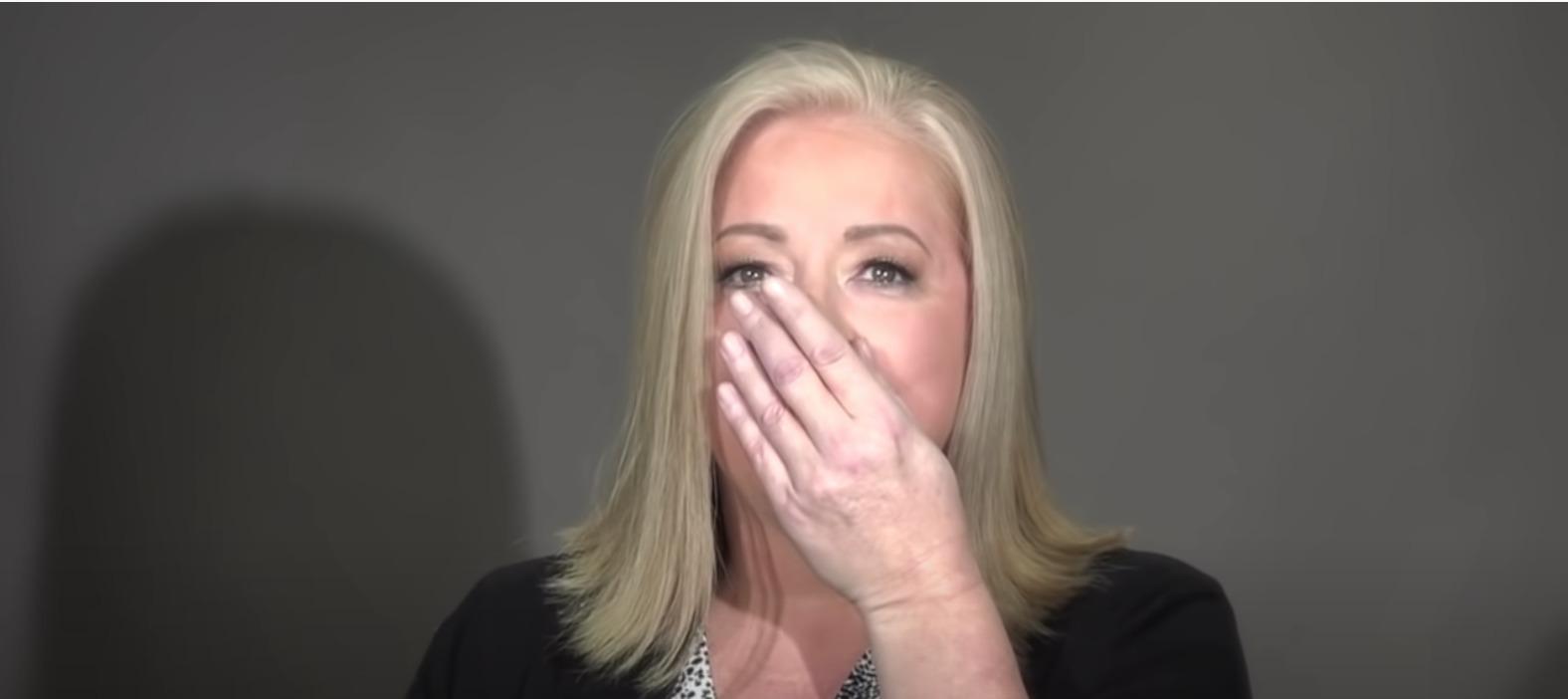 kobieta ręką zakrywa twarz